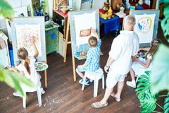 Children Painting in Art Studio. High angle portrait of three children painting on easels during art class and teacher watching them in cozy studio decorated stock photo