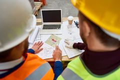 Construction Workers Looking at Plans. High angle portrait  of two unrecognizable construction workers looking at blueprints and floor plans on site Stock Image