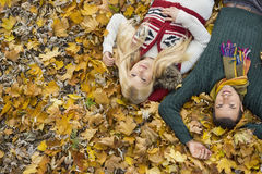 High angle portrait of young couple lying on autumn leaves at park Stock Photography