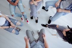 High angle of teenagers meeting. High angle of rehab specialist and rebellious teenagers sitting in a circle during a meeting Royalty Free Stock Photos