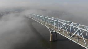 High Angle Reverse Aerial View of Foggy Bridge Over Ohio River. A high angle slow reverse aerial establishing shot of a bridge over the Ohio River on a foggy stock video
