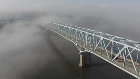 High angle reverse aerial view of foggy bridge Over Ohio river. A high angle slow reverse aerial establishing shot of a bridge over the Ohio River on a foggy stock footage