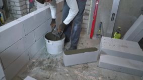 High angle shot of builder putting mortar on side of aerated concrete block. High angle shot of young caucasian builder putting mortar on side of aerated stock footage