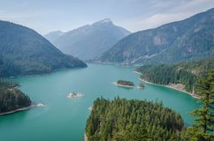 High angle shot of the Diablo Lake in the middle of forested mountains under a blue sky