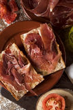 Catalan pa amb tomaquet with serrano ham. High-angle shot of an earthenware plate with typical catalan pa amb tomaquet, bread with tomato dressed with olive oil stock image