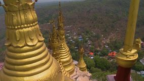 Golden stupas built close to each other. A high angle shot of golden stupas in a temple built close to each other and descending down a hill stock video footage