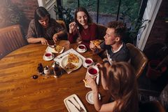 High angle shot of group of best friends having dinner at round table together talking and smiling in cozy cafe.  Royalty Free Stock Photography