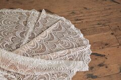 High angle shot of the lace train of the white wedding dress on the wooden floor
