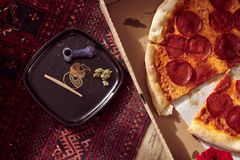 Free High Angle Shot Of A Pepperoni Pizza And A Plate With Marijuana Blunts And Pieces Of Dry Cannabis Stock Photo - 165112030