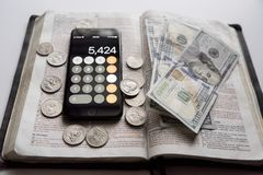 High angle shot of an open bible with dollar bills and smartphone on top