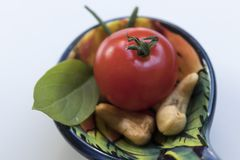 Little tomato with some cashew nuts, basil and rosemaries on a b. High-angle shot. Seen from above. Close-up Royalty Free Stock Images