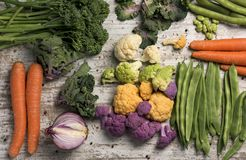 Raw vegetables on a white rustic wooden table. High angle shot of some different raw vegetables, such as cauliflower of different colors, broccolini, fava beans Royalty Free Stock Photography