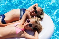 Happy girls relaxing on mattress in swimming pool Stock Photos