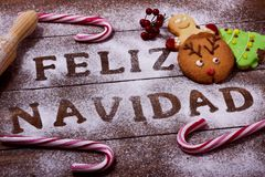 Text feliz navidad, merry christmas in spanish. High-angle shot of a wooden table sprinkled with icing sugar or flour where you can read the text feliz navidad Stock Image