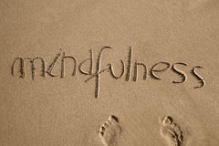 Word mindfulness in the sand. High-angle shot of the word mindfulness written in the sand of a beach and a pair of human footprints Stock Photography