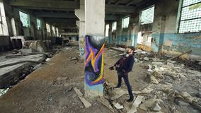 High angle shot of young urban artist decorating high column in old damaged building with abstract image. Modern art. Professional street painter, creativity stock video footage