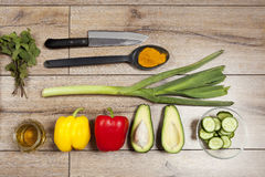 High Angle Still Life View of Knife and Wooden Cutting Board Surrounded by Fresh Herbs. Assortment of Raw Vegetables on Rustic Woo Stock Photography