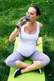 Thirsty pregnant woman drinking water after yoga workout Royalty Free Stock Photography