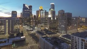 A high wide angle shot of downtown Minneapolis cityscape illuminating during twilight 4k uhd timelapse. A high angle timelapse shot of downtown Minneapolis and stock footage