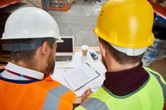 Construction Workers Discussing Plans. High angle of two unrecognizable construction workers looking at blueprints and floor plans on site royalty free stock images