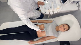 High angle of ultrasound examination of the abdominal cavity. High angle of the doctor making the  ultrasound examination of the abdominal cavity of a woman stock video footage
