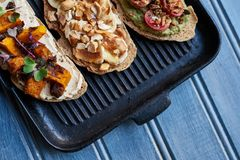 Skillet cooked open faced sandwiches on a rustic blue table Royalty Free Stock Photos