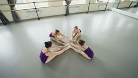 High angle view of flexible ballet dancers doing head-to-knee bends sitting on floor in studio stretching legs and back stock video