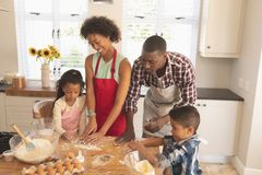 African American family baking cookies in kitchen. High angle view of African American family baking cookies in kitchen at home stock images