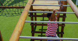High angle view of African American schoolboy playing on horizontal ladder in school playground 4k. High angle view of African American schoolboy playing on stock video
