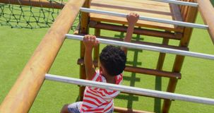 High angle view of African American schoolboy playing on horizontal ladder in school playground 4k stock video footage