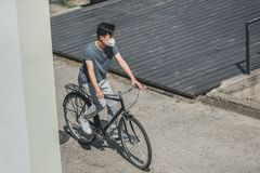 High angle view of asian teen in protective mask riding bicycle in city air. Pollution concept stock photo