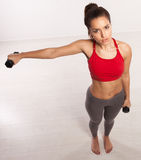 Athletic woman working with dumbbells Stock Photography
