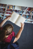 High angle view of attentive schoolgirl reading book in library Royalty Free Stock Photos