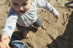 High angle view of a baby boy having his firts steps in the sand Stock Photo