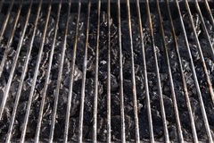 Grill Grate and LAva Stones. High angle view of a barbecue grill grate with lava stones beneath it, lit by sunlight Royalty Free Stock Photos