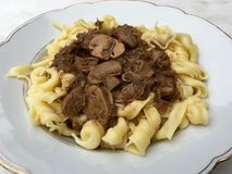 High angle view of beef goulash with mushrooms and noodles served on white plate. In closeup Royalty Free Stock Photos