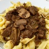 High angle view of beef goulash with mushrooms and noodles served on white plate. In closeup Stock Photography