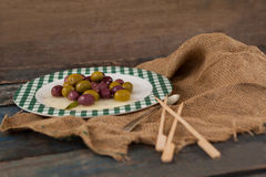 High angle view of black and green olives served in plate. On wooden table Royalty Free Stock Photography