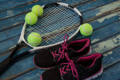 High angle view of black sports shoes by tennis balls and racket Royalty Free Stock Image