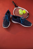High angle view of blue sports shoes by tennis racket and balls Royalty Free Stock Photo