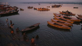 High angle view of boats sailing through Ganges river in Varanasi at sunset. VARANASI, INDIA - 22 FEBRUARY 2015: People bathing in Ganges river in Varanasi at stock video