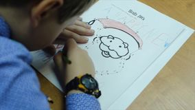 High angle view of boy drawing with color pencil on paper at desk in classroom. Clip. A cute little boy drawing with a. Pencil close up Stock Photos