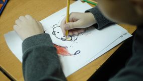 High angle view of boy drawing with color pencil on paper at desk in classroom. Clip. A cute little boy drawing with a stock photos