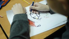High angle view of boy drawing with color pencil on paper at desk in classroom. Clip. A cute little boy drawing with a. Pencil close up Royalty Free Stock Image