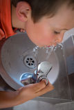 High angle view of boy driniking water from faucet. At school Stock Photos