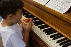 High angle view of boy eating apple while sitting by piano Stock Photo