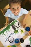 High angle view of a boy painting and smiling Royalty Free Stock Images