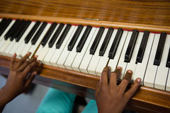 High angle view of boy playing piano while sitting in classroom Stock Photo
