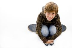 High angle view of boy sitting on skateboard Royalty Free Stock Image