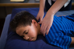 High angle view of boy sleeping on bed while receiving back massage from female therapist Stock Image